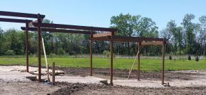 Pergola under construction showing orchard in background
